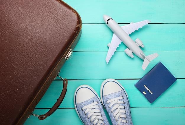 Vieux bagages, figurine d'avion, passeport, baskets sur plancher en bois bleu