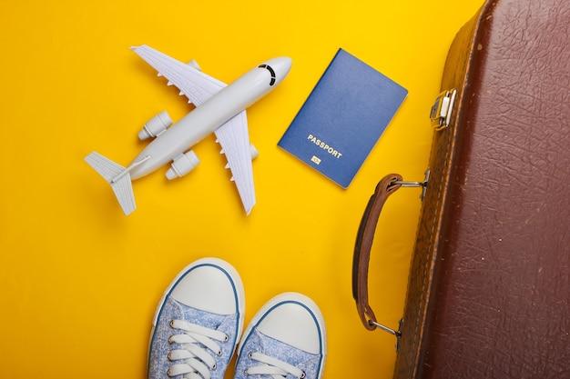 Vieux bagages, figurine d'avion, passeport, baskets sur surface jaune