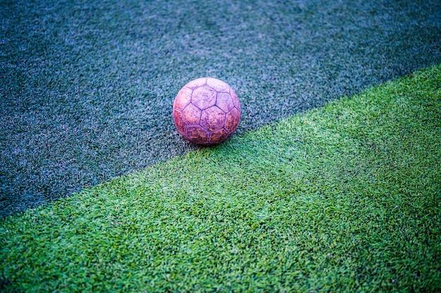 Vieux ballon de foot sur l'herbe