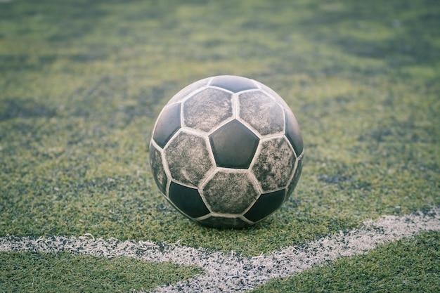 Vieux ballon de foot sur terrain de foot