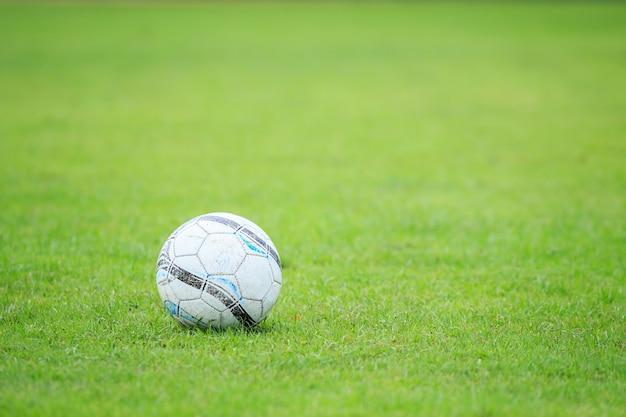 Vieux ballon de football blanc sur le terrain et flou de joueur dans le stade