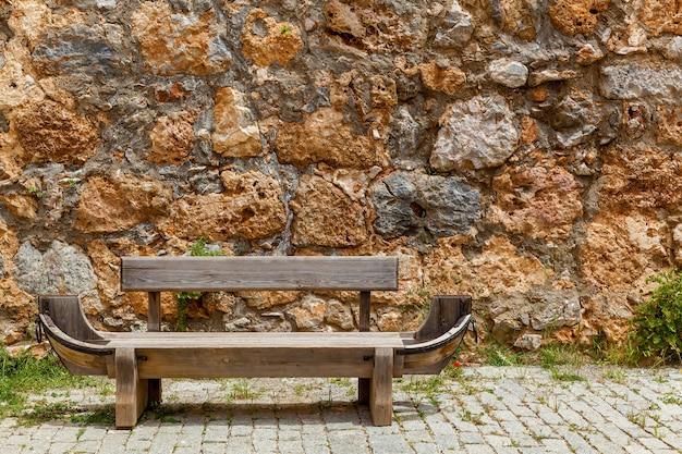 Un vieux banc en bois en forme de bateau debout dans une rue devant un mur de pierre.