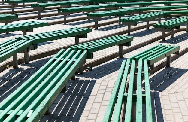 Vieux bancs en bois de couleur verte, vieux bancs situés dans un amphithéâtre d'été sans toit