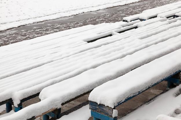 Vieux bancs en bois dans le stade, recouverts de neige en hiver