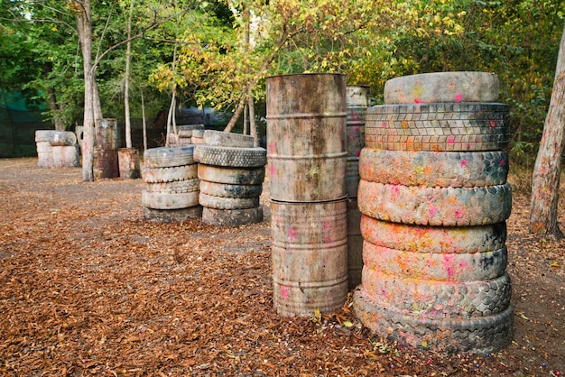 Vieux barils rouillés et pneus endommagés à la base de paintball où se cachent les joueurs excités