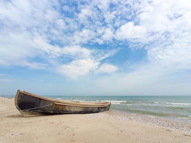 Vieux bateau en bois au bord de la mer, ciel nuageux, temps ensoleillé.