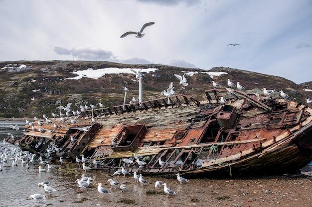 Vieux bateau de pêche abandonné abandonné sur le rivage