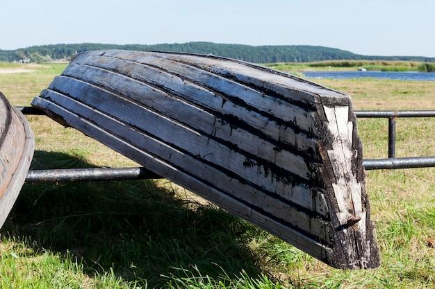 De vieux bateaux en bois sont séchés sur le rivage en été, un gros plan près du lac et un petit village où les habitants pratiquent la pêche