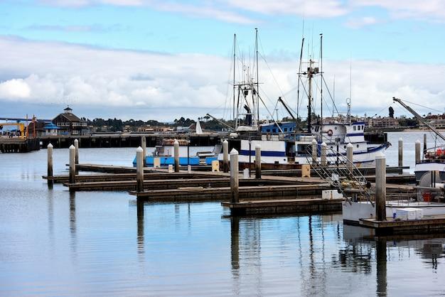Vieux bateaux dans un port et une jetée dans la soirée