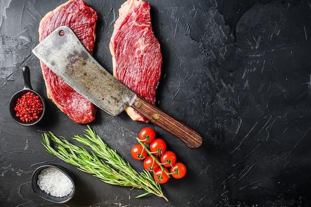 Vieux boucher coupé sur des steaks de bœuf picanha crus avec du romarin, du poivre et du sel