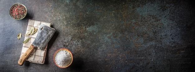 Vieux boucher de viande sur planche de béton foncé avec épices sel et poivre.