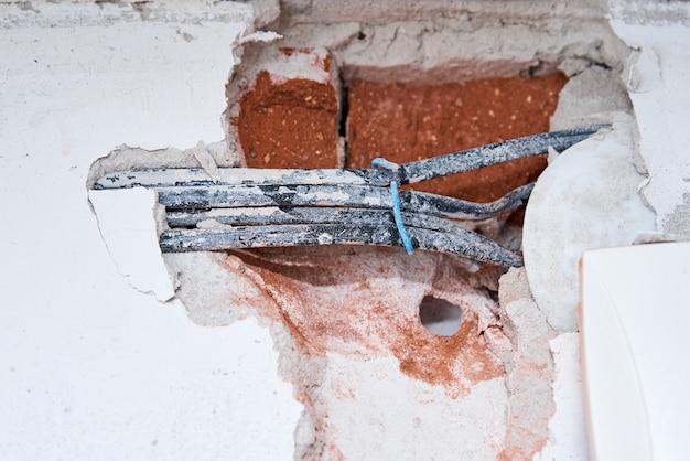 Vieux câbles électriques dans un mur de briques. câblage de danger