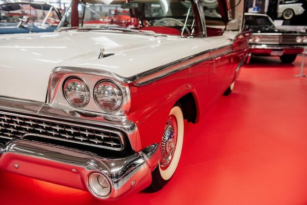 Vieux cabriolet blanc rétro garé sur la tuile rouge au salon de l'automobile