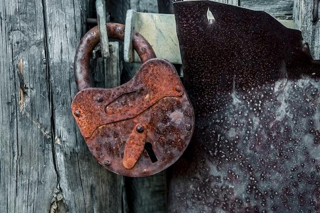 Vieux cadenas rouillé sur la fermeture de la porte