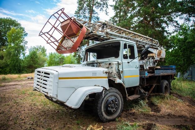 Vieux camion abandonné dans une clairière, équipement de grunge, démonté cassé