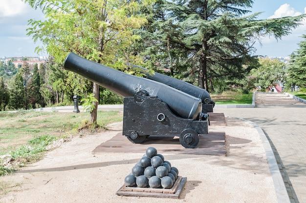 Vieux canons sur des chariots en bois et des noyaux de fort défensif.