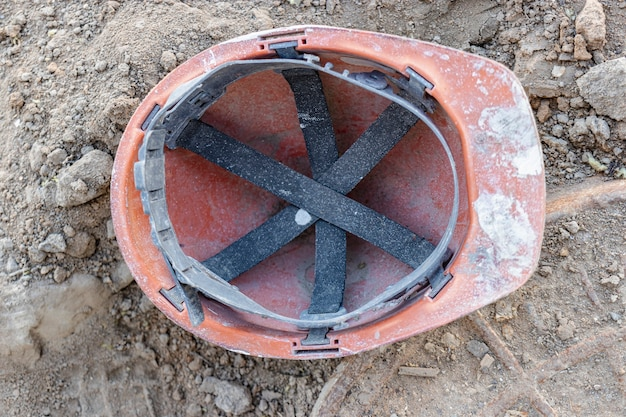 Vieux casque de travail sale laissé sur le terrain du chantier de construction.