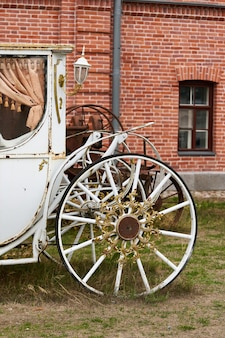 Vieux chariot blanc sur le fond d'un bâtiment en brique rouge. chariot vintage blanc