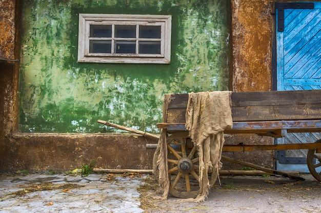 Vieux chariot en bois dans le village sur le fond d'une vieille maison. grande porte en bois bleue.