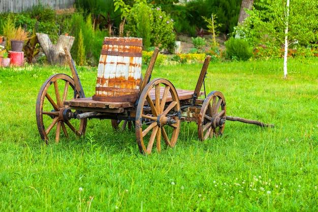 Vieux chariot en bois avec un fût sur l'herbe verte