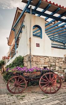 Vieux chariot avec des pots de fleurs, chariot en bois avec des fleurs au coucher du soleil.