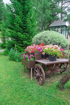 Vieux chariot vintage en bois avec pots de fleurs et boîtes