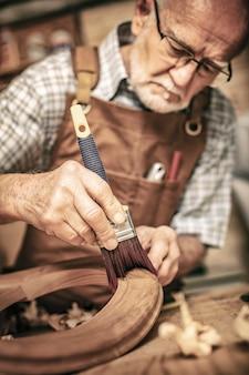 Vieux charpentier au travail