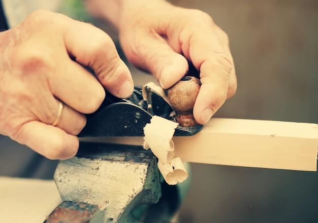Vieux charpentier travaillant avec du bois