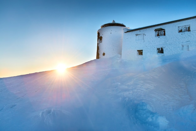 Vieux château au sommet d'une montagne couverte de neige en hiver au coucher du soleil et au soleil brillant