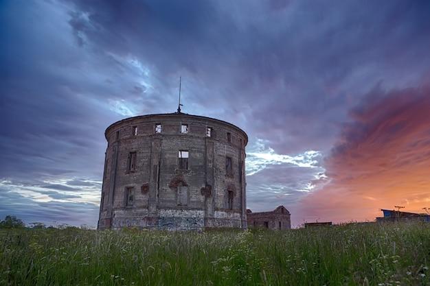 Vieux château d'eau en ruine dans le canton de verevo, oblast de léningrad sous un ciel coloré à minuit du solstice d'été