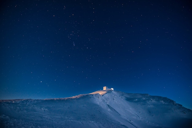 Vieux château sur la montagne d'hiver avec de la neige la nuit sous un ciel bleu foncé avec de nombreuses étoiles