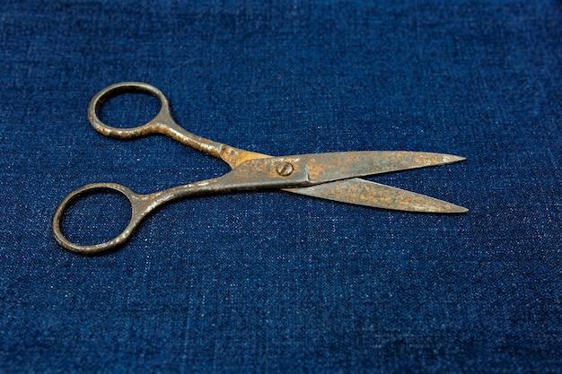 Vieux ciseaux vintage se trouvent sur un fond de tissu. l'outil du tailleur.