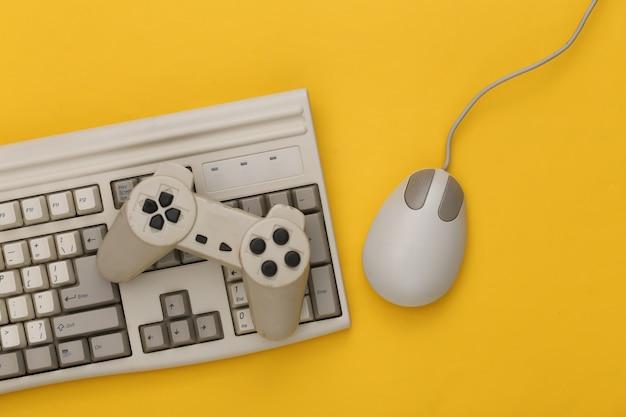 Vieux clavier, manette de jeu et souris pc sur fond jaune. jeu rétro. années 80. vue de dessus