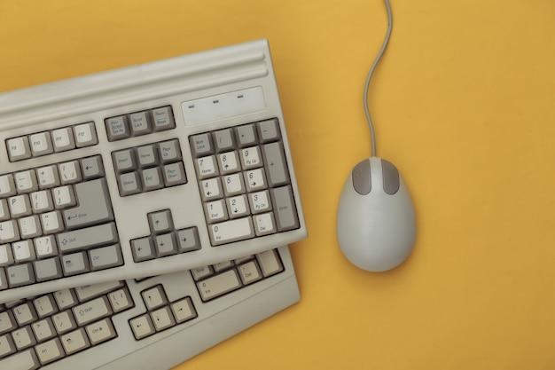 Vieux clavier et souris pc sur fond jaune. vue de dessus. mise à plat