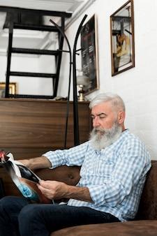 Vieux client lisant un magazine dans un salon de coiffure