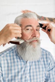 Vieux client se faisant couper les cheveux au salon de coiffure