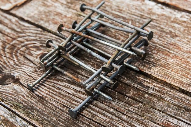 Vieux clous rouillés sur fond en bois. clous sur table en bois