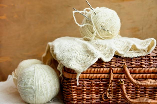 Vieux coffre de passe-temps en osier vintage avec des pointes de laine blanche, travaux d'aiguille sur fond de bois rustique