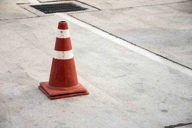 Vieux cône de circulation sur route en béton.