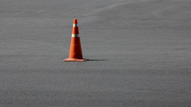 Vieux cône de signalisation orange sur la route goudronnée