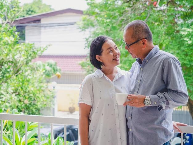 Vieux couple buvant du café sur le balcon