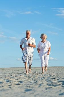 Vieux couple courant sur une plage par une journée ensoleillée