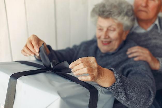 Vieux couple élégant assis à la maison avec des cadeaux de noël