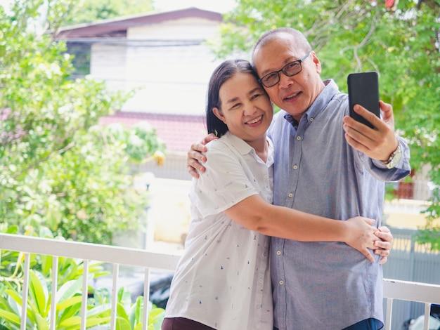 Vieux couple embrassé sur le balcon