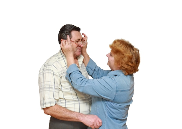 Vieux couple, la femme met ses lunettes de mari. isolé.