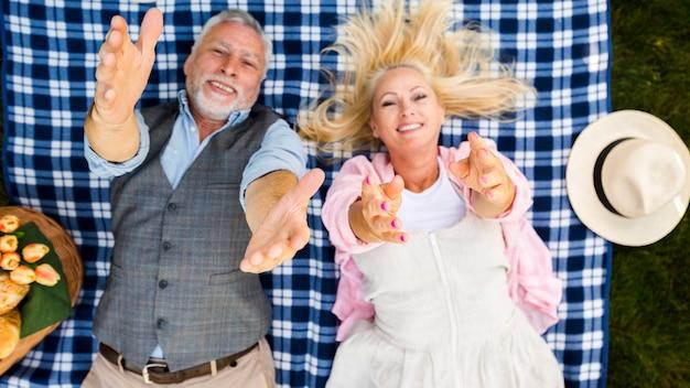 Vieux couple levant les bras à la caméra vue de dessus