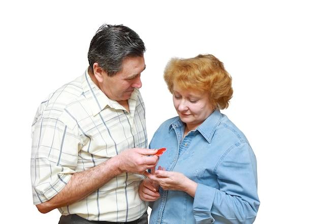 Vieux couple, mari donne à sa femme un petit coeur. isolé sur blanc