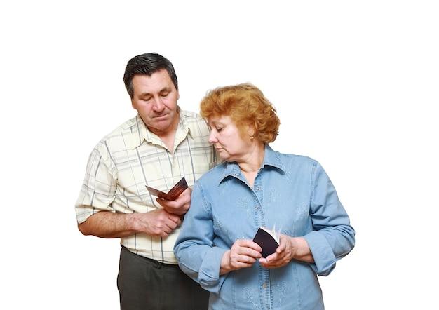 Un vieux couple marié regarde les pièces d'identité de la pension avec le sourire. isolé.