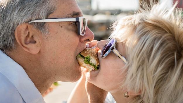 Vieux couple partageant un hamburger à l'extérieur