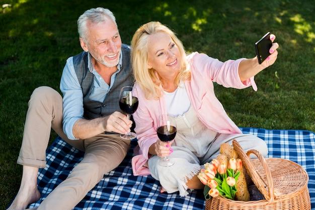 Vieux couple prenant un selfie en hauteur